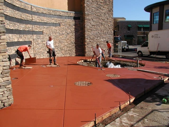 The Davis Colors' Brick Red concrete pigment at the Bridgeport Village Shopping Center located in Tigard, Oregon is being finished by the concrete finishers