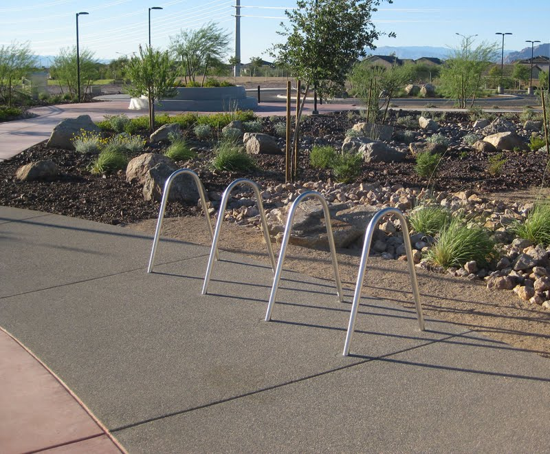 This concrete bike parking area at the Heritage Bark Park in Henderson, NV was colored with Davis Colors' Mesa Buff and finished with an exposed aggregate.  The walkways were colored with Davis Colors' Baja Red. The landscape design was done by the Design Workshop. To contact the Design Workshop visit their website   www.designworkshop.com or call them at 775-588-5929. To learn more about this project go to http://www.landscapeonline.com/research/article/14721.