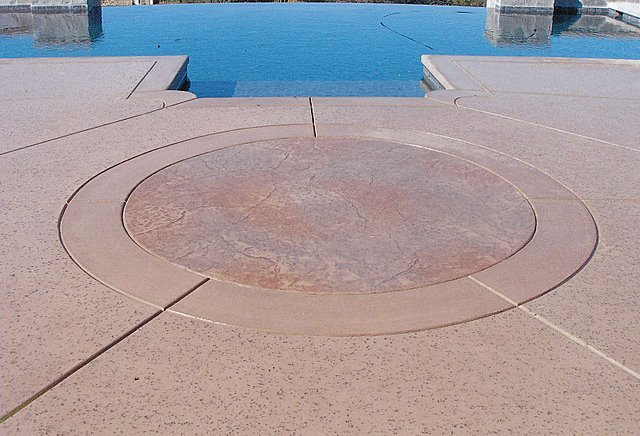 This decorative concrete stamped pool deck that was colored with Davis Colors Sandstone www.daviscolors.com. For the stamped portion they used an old granite pattern with a light gray and mesa buff release agent.