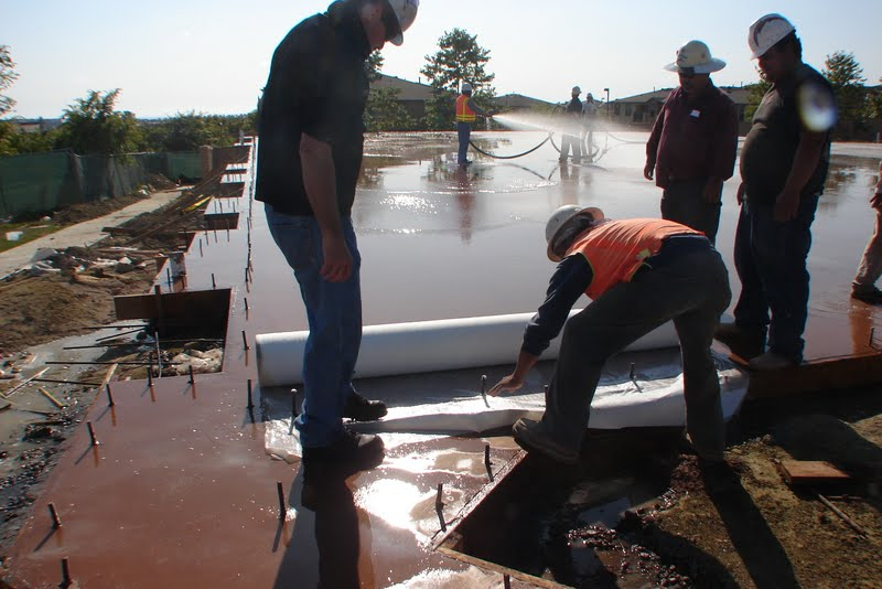 "The wet curing process begins with covering the surface of the concrete with a 1/8"" to 1/4"" layer of water. Here the contractors are starting to roll out McTech Group's UltraCure NCF™ curing blanket. This curing method is designed to provide thorough hydration and even curing."