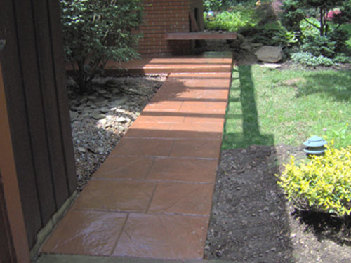This stamped walkway was integrally colored with Davis Colors' Terra Cotta concrete color and stamped with a Walkway Stone pattern. The release agent was a Smokey Beige color. The concrete work was done by Butch Bando Concrete, Inc. located in Galena, Ohio. You can reach Butch Bando Concrete, Inc. by visiting their website at www.butchbandoconcrete.com or by calling them at 740-548-7322. These photos were provide by Butch Bando Concrete, Inc. and are being used with their permission.